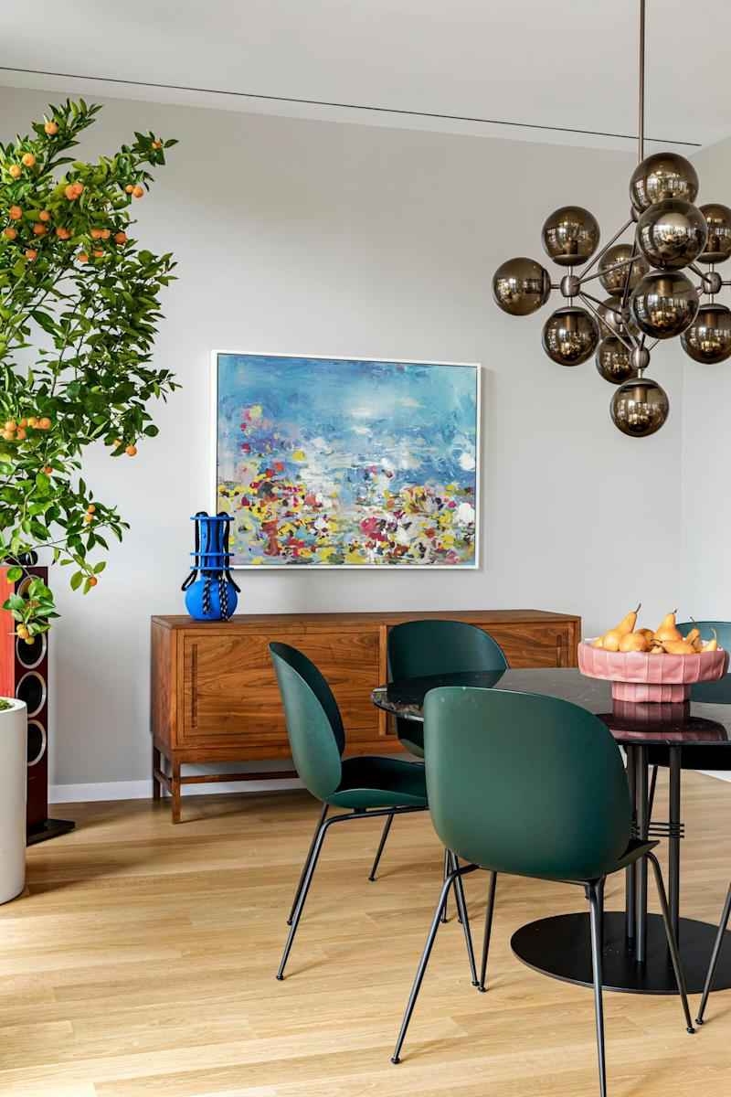 The dining area's round, black marble dining table and green Beetle dining chairs are both by Danish brand Gubi, and were already owned by Elle and her husband.