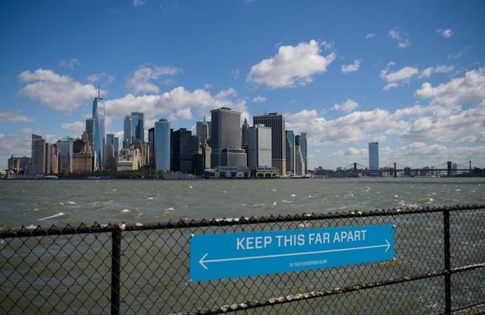 <p>A sign to promote social distancing is seen on Governors Island, New York</p> (AFP via Getty Images)