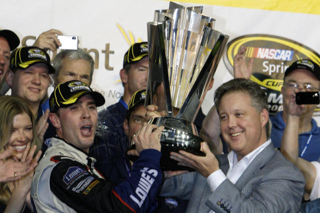 FILE - In this Nov. 22, 2009, file photo, Jimmie Johnson, left, raises the trophy with NASCAR chairman Brian France, right, after winning the NASCAR Sprint Cup Series season championship at Homestead-Miami Speedway in Homestead, Fla. Jimmie Johnson is the latest NASCAR superstar to climb out of his car, with the seven-time champion announcing Wednesday, Nov. 20, 2019, that 2020 will be his final season of full-time racing. (AP Photo/Chuck Burton, File)