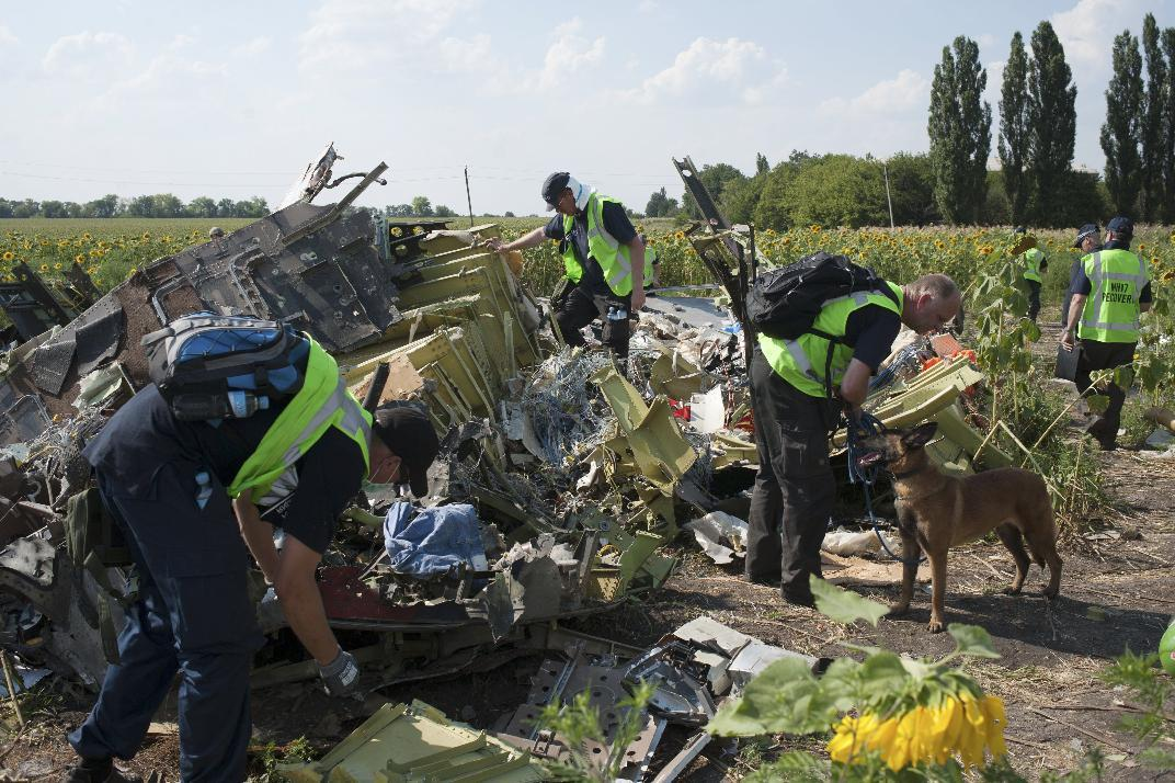 "FILE - In this Tuesday, Aug. 5, 2014 file photo, Australian, Malaysian and Dutch investigators examine pieces of the downed Malaysia Airlines Flight 17 plane, near the village of Rossipne, Donetsk region, eastern Ukraine. The Dutch team investigating the downing of the Malaysian jetliner over Eastern Ukraine said Tuesday, Sept. 9, 2014, the crash was likely caused by the plane being hit by multiple ""high-energy objects from outside the aircraft."" The preliminary report published Tuesday by the Dutch Safety Board stopped short of saying the Boeing 777 was shot down by a surface-to-air missile, but its findings appear to point to that conclusion. (AP Photo/File)"