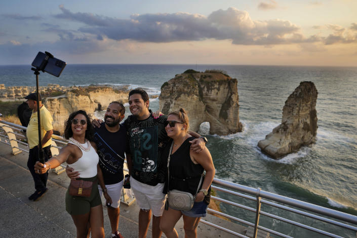 Egyptian tourists take a selfie in front the Rawcheh Sea Rock as the sun sets over the Mediterranean Sea in Beirut, Lebanon, Friday, July 2, 2021. With their dollars trapped in the bank, a lack of functioning credit cards and travel restrictions imposed because of the pandemic, many Lebanese who traditionally vacationed over the summer at regional hotspots are also now turning toward domestic tourism. (AP Photo/Hassan Ammar)
