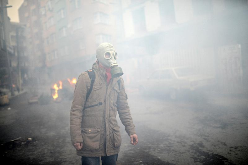 A man wearing a tear gas mask is seen on March 11, 2015 in Istanbul, during clashes following a protest in memory of a teenager killed in 2013 anti-government demonstrations and whose death has become a rallying cause for opponents of the president