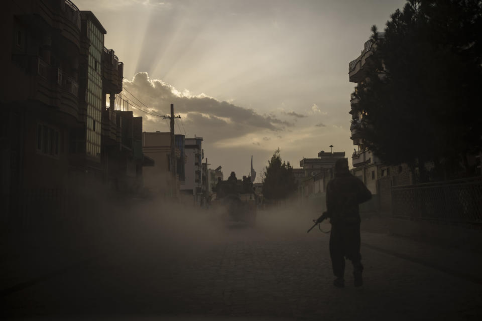 A Taliban fighter walks on the side of a road as a Humvee carrying other fighters drives by in Kabul, Afghanistan, Tuesday, Sept. 21, 2021. (AP Photo/Felipe Dana)
