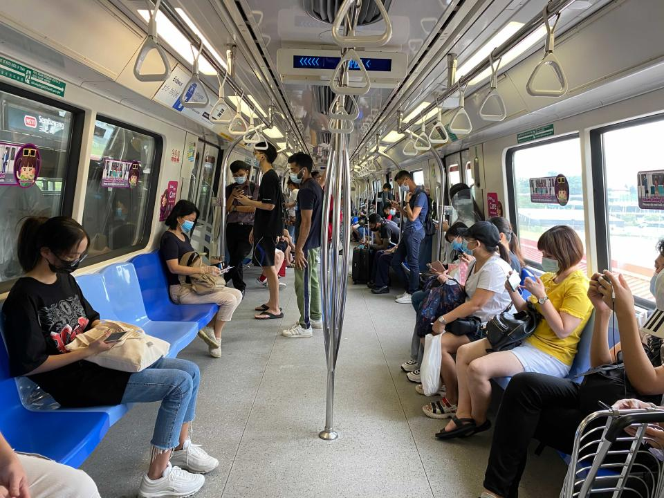 Commuters wear face masks and practice social distancing while onboard a subway Wednesday, May 19, 2021 in Singapore. Across much of Asia, taxi drivers are starved for customers, weddings are suddenly canceled, schools are closed, and restaurant service is restricted as the coronavirus comes surging back in countries where it had seemed to be well under control. (AP Photo/Zen Soo)