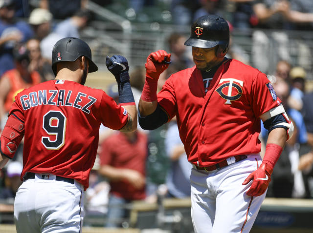 Minnesota Twins designated hitter Nelson Cruz, right, celebrates with Marwin Gonzalezafter hitting a solo home run off a pitch by Seattle Mariners pitcher Yusei Kikuchi during the third inning of a baseball game Thursday, June 13, 2019, in Minneapolis. (AP Photo/Craig Lassig)