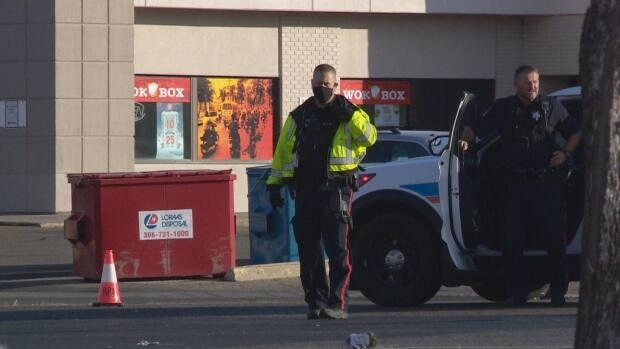 A member of the Regina Police Service is seen wearing a mask in a CBC file photo. The Saskatchewan Association of Chiefs of Police says front-line officers should be considered for priority as the province continues its vaccine rollout, considering they're regularly dealing with COVID-19 enforcement measures. (CBC - image credit)