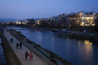 People stroll along the Kamo River in Kyoto, Japan, March 18, 2020. Kyoto's city government has an emergency fund for small to medium-size businesses who suffered sharp sales decline since the coronavirus outbreak. (AP Photo/Jae C. Hong)