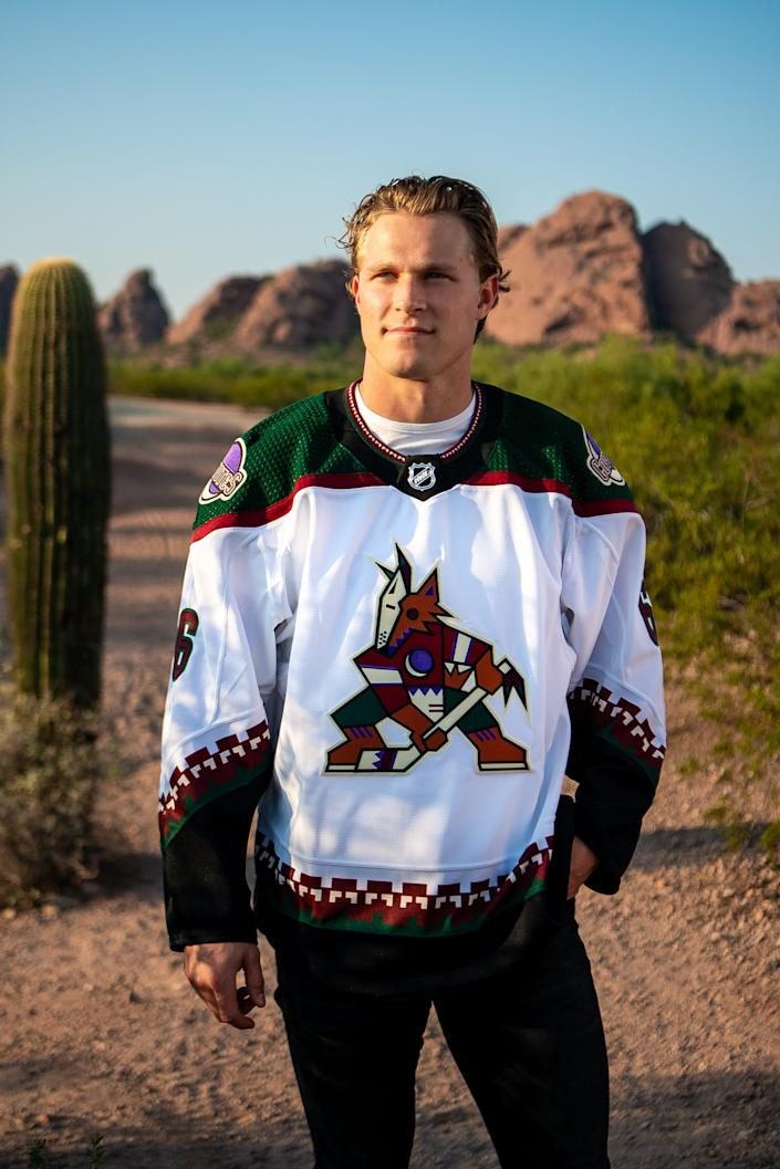 Coyotes defenseman Jakob Chychrun models the team's repurposed white road jersey with Kachina logo.