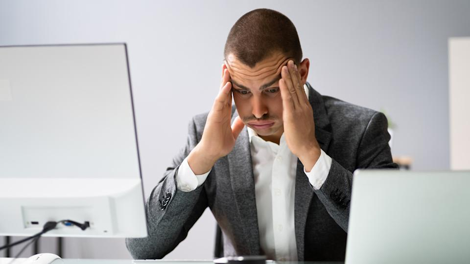 Upset worried man using laptop In office. (Getty Images)