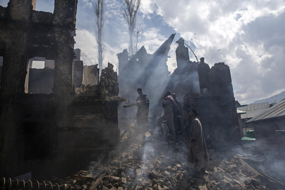 Kashmiri men dismantle a portion of a house destroyed in a gunbattle in Tral village, south of Srinagar, Indian controlled Kashmir, March 4, 2019. The image was part of a series of photographs by Associated Press photographers which won the 2020 Pulitzer Prize for Feature Photography. (AP Photo/Dar Yasin)