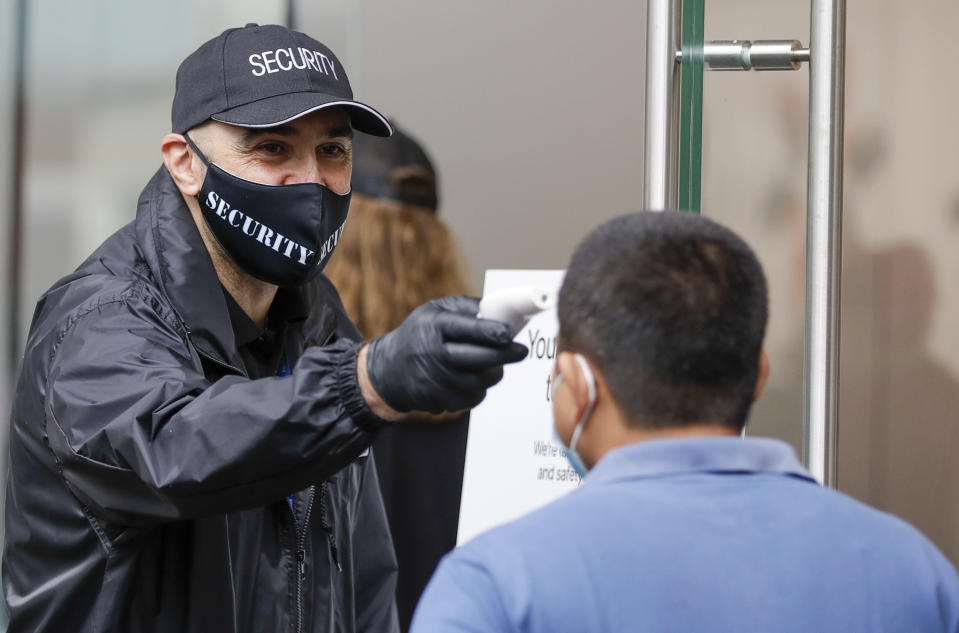 A security guard takes the temperature of a customer at a shopping precinct in Sydney, Australia, Sunday, Jan. 3, 2021. Masks have been made mandatory in shopping centers, on public transport, in entertainment venues such as a cinema, and fines will come into effect on Monday as the state government responds to the COVID-19 outbreak on Sydney's northern beaches, which is suspected to have also caused new cases in neighboring Victoria state. (AP Photo/Mark Baker)