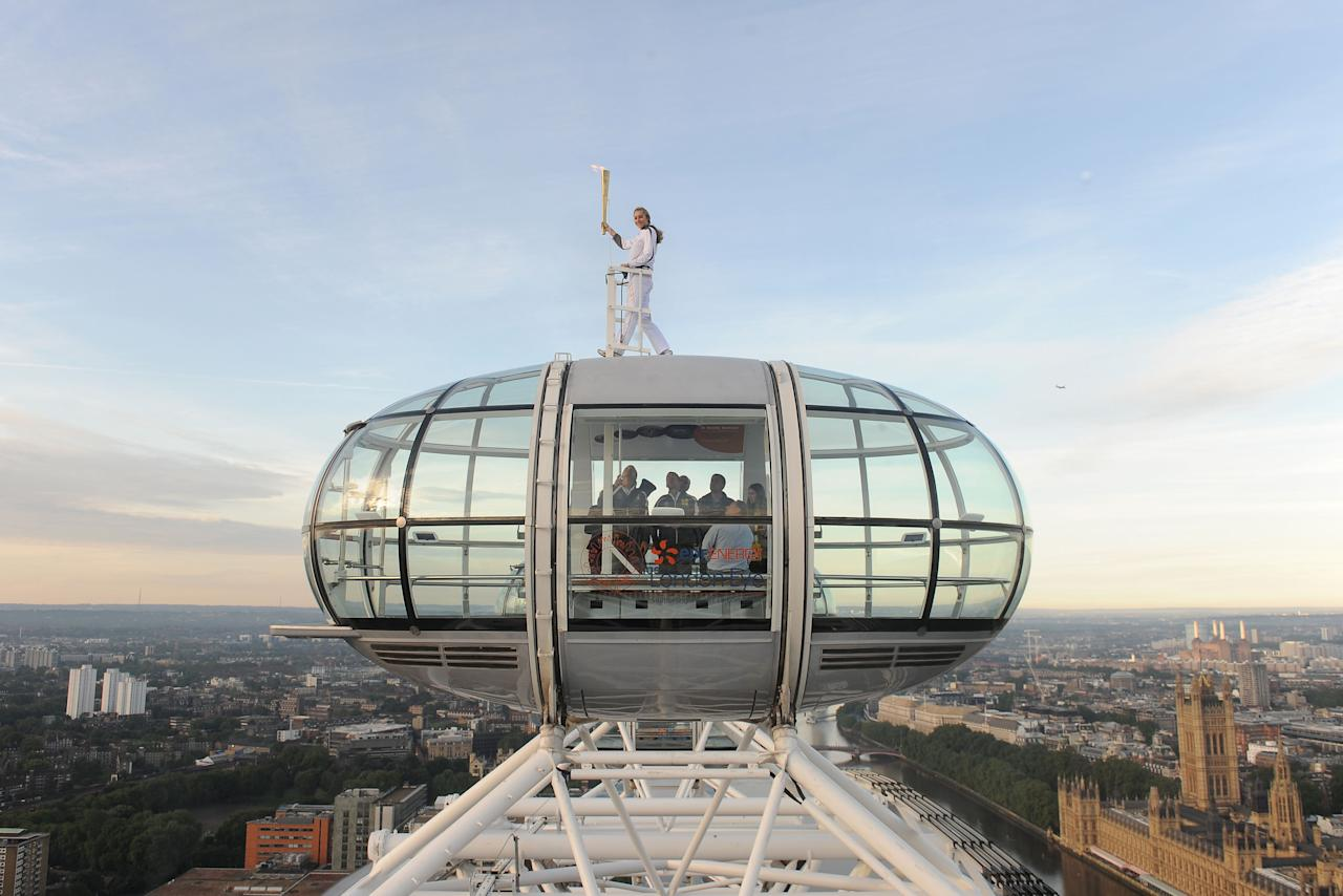CORRECTS BYLINE TO JOE GIDENS, NOT LEWIS WHYLD- In this photo provided by LOCOG, Amelia Hempleman-Adams poses with the Olympic Flame on top of a London Eye pod on the Torch Relay leg through London. Opening Ceremonies for the 2012 London Olympics will be held Friday July 27. (AP Photo/LOCOG, Joe Gidens)