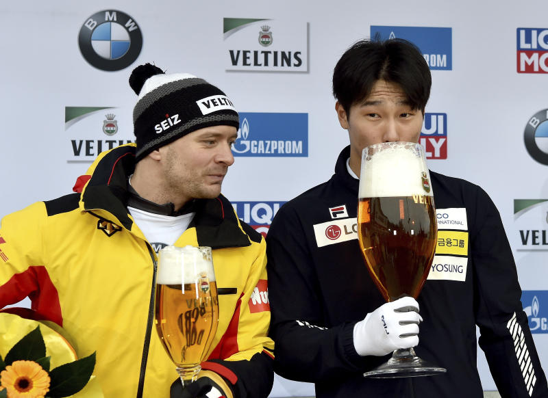 Yun Sung Bin from South Korea zips from a giant glass of beer after winning the men's Skeleton world cup in Winterberg, Germany, Sunday, Jan.5, 2019.  Germany's Axel Jungk at left.(Caroline Seidel/dpa via AP)