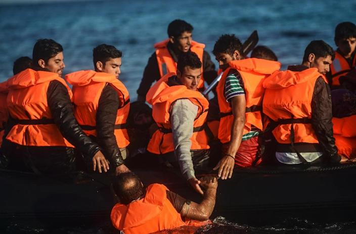 Migrants and refugees disembark on a raft to the Greek island of Chios from Cesme in the Turkish province of Izmir on November 5, 2015 (AFP Photo/Bulent Kilic)