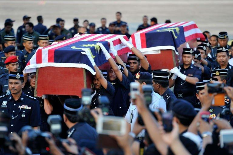 Malaysian police carry the coffins of two dead officers killed in an ambush in Semporna, on March 4, 2013