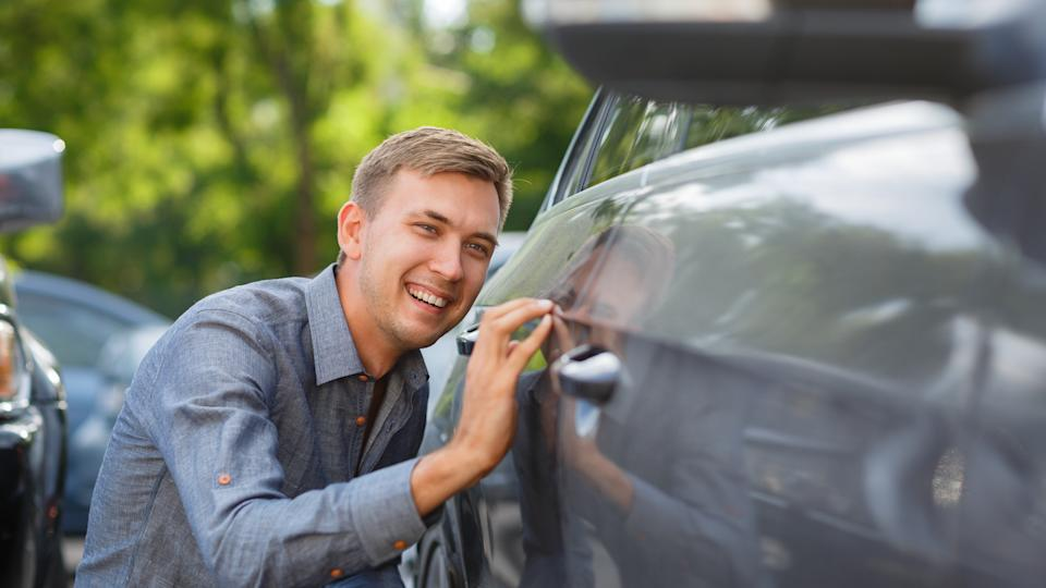 man checking out used car trim