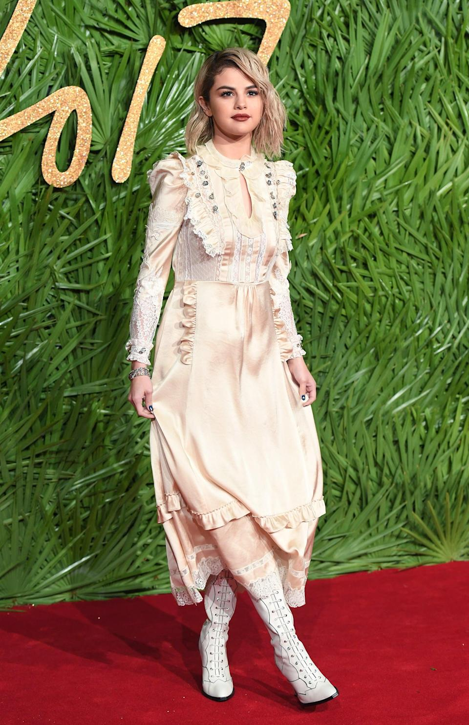 """<p><a href=""""https://www.popsugar.com/fashion/Selena-Gomez-Coach-Dress-Fashion-Awards-2017-44327073"""" class=""""link rapid-noclick-resp"""" rel=""""nofollow noopener"""" target=""""_blank"""" data-ylk=""""slk:Selena wore a full-on custom Coach look"""">Selena wore a full-on custom Coach look</a> by Stuart Vevers for the Fashion Awards 2017 in London in December 2017. She picked up her Victorian-inspired dress to reveal white hot leather lace-up boots, which we could imagine with a denim skirt and tee, too.</p>"""