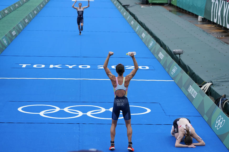 Gold medal winner Flora Duffy of Bermuda cheers on bronze medalist Katie Zaferes of The United States as she approaches the finish, while silver medalist Georgia Taylor-Brown of Great Britain collapses on the ground after finishing during the women's individual triathlon competition at the 2020 Summer Olympics, Tuesday, July 27, 2021, in Tokyo, Japan. (AP Photo/Charlie Riedel)(AP Photo/David Goldman)