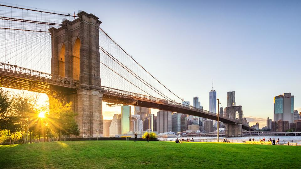 View of Brooklyn Bridge and Lower Manhattan at sunset with sun Flare and a blank space.