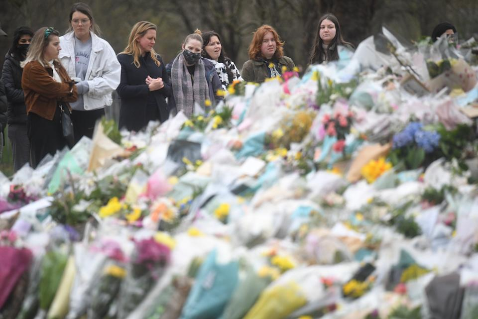 People viewing floral tributes left at the bandstand in Clapham Common, London, for Sarah Everard. Pc Wayne Couzens, 48, appeared at the Old Bailey in London charged with the kidnap and murder of the 33-year-old. Picture date: Sunday March 21, 2021.