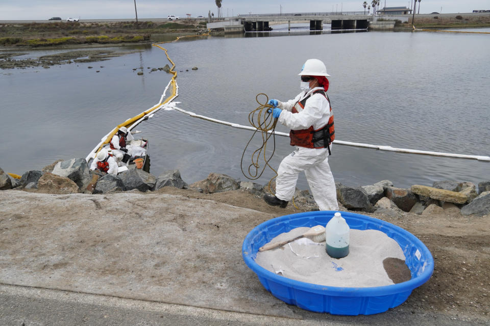 Cleanup crews, wearing protective suits, retrieve tools with oil deposits around the Talbert Marsh in Huntington Beach, Calif., Wednesday, Oct. 6, 2021. An oil spill sent up to 126,000 gallons of heavy crude into the ocean. It contaminated the sands of famed Huntington Beach and other coastal communities. (AP Photo/Eugene Garcia)