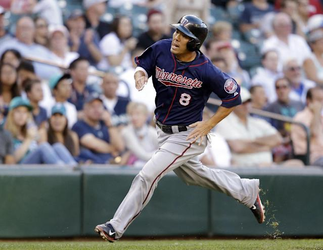 Minnesota Twins' Kurt Suzuki comes around to score against the Seattle Mariners in the second inning of a baseball game Wednesday, July 9, 2014, in Seattle. (AP Photo/Elaine Thompson)