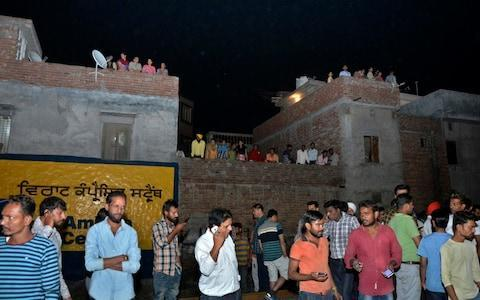 A crowd gathers at the site of the train accident - Credit: Prabhjot Gill/AP