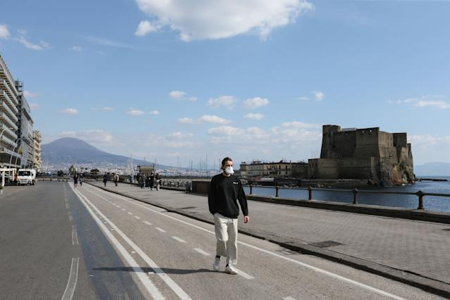 A man wearing a respiratory mask as part of precautionary measures against the spread of the new COVID-19 coronavirus, walks along the seafront by Castel dell'Ovo in Naples on March 10, 2020. (Credit: Carlo Hermann/AFP)
