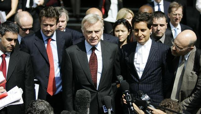 Max Mosley (centre) speaks to the press as he leaves the High Court in London after winning his case against the News of the World