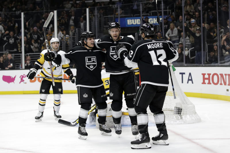 Los Angeles Kings' Trevor Lewis, center, celebrates his goal with Blake Lizotte, left, and Trevor Moore (12) during the second period of an NHL hockey game against the Pittsburgh Penguins Wednesday, Feb. 26, 2020, in Los Angeles. (AP Photo/Marcio Jose Sanchez)
