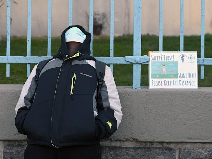 a student stands against school walls next to a sign that reads 'safety first! keep social distance'