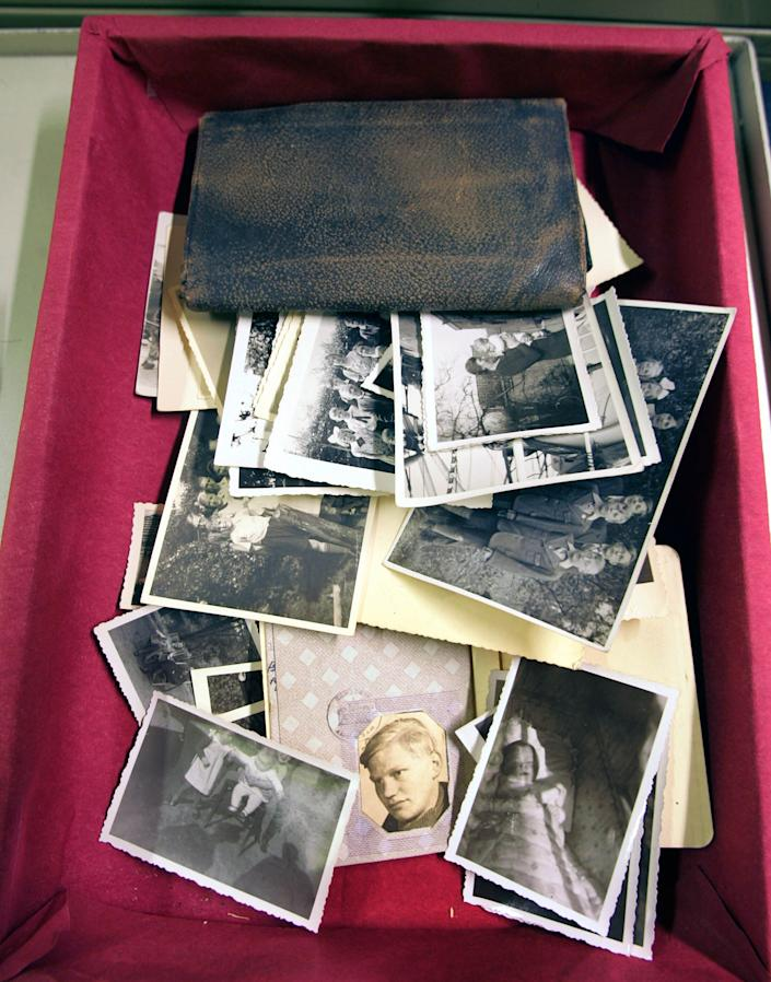 This Nov. 9, 2006 file photo shows a photograph of Cornelis Brouwenstijn, bottom center, with other prints and a wallet in the archive at the International Tracing Service (ITS) in Bad Arolsen, Germany. (AP Photo/Michael Probst, File)