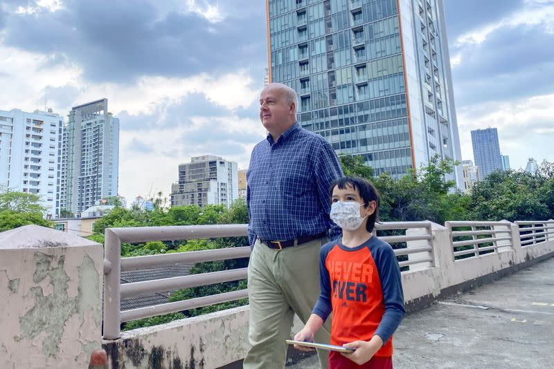 Paul Risley, a U.S. citizen chair of Democrats Abroad, walks with his son during an interview with Reuters in Bangkok