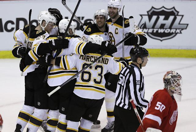 Detroit Red Wings goalie Jonas Gustavsson (50) of Sweden skates by as the Boston Bruins celebrate their 3-2 overtime win in Game 4 of a first-round NHL hockey playoff series in Detroit, Thursday, April 24, 2014. (AP Photo/Carlos Osorio)