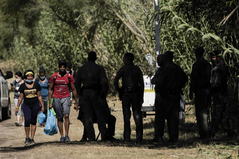 """Cuban nationals, left, walk near Texas Department of Public Safety officials, right, on a road along the Rio Grande after crossing the river while seeking asylum, Thursday, Sept. 23, 2021, in Del Rio, Texas.The """"amistad,"""" or friendship, that Del Rio, Texas, and Ciudad Acuña, Mexico, celebrate with a festival each year has been important in helping them deal with the challenges from a migrant camp that shut down the border bridge between the two communities for more than a week. Federal officials announced the border crossing would reopen to passenger traffic late Saturday afternoon and to cargo traffic on Monday. (AP Photo/Julio Cortez)"""