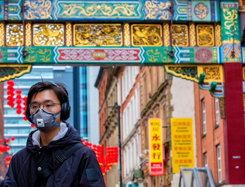 A passerby wearing a face mask in Manchester's Chinatown&nbsp;<br /> (Photo: Peter Byrne - PA Images via Getty Images)