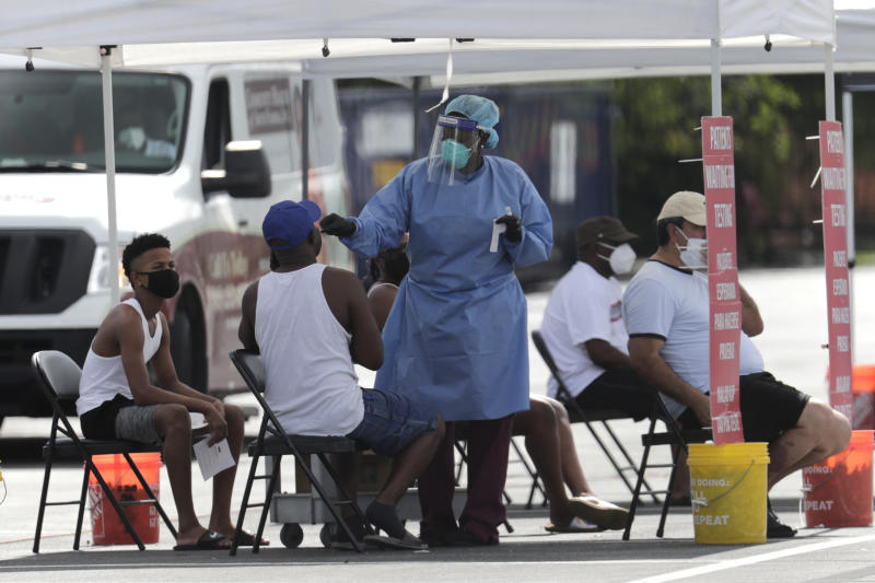 A health care worker administers a COVID-19 test at a site sponsored by Community Heath of South Florida at the Martin Luther King, Jr. Clinica Campesina Health Center, during the coronavirus pandemic, Monday, July 6, 2020, in Homestead, Fla. (AP Photo/Lynne Sladky)