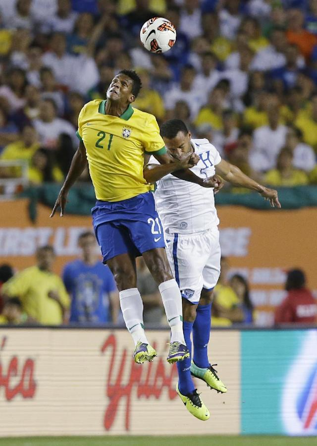 Brazil forward Jo (21) heads the ball over Honduras defenseman Victor Bernardez during the first half of an international friendly soccer game, Saturday, Nov. 16, 2013, in Miami Gardens, Fla. (AP Photo/Wilfredo Lee)