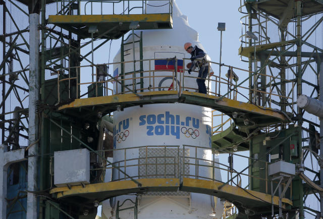 A Baikonur Cosmodrome staff member works at Russia's Soyuz-FG booster rocket, emblazoned with the emblem of the Winter Olympics in Sochi, loaded with Soyuz TMA-11M space capsule that will carry new crew to the International Space Station (ISS) as the rocket is transported from hangar to the launch pad at the Russian leased Baikonur cosmodrome, Kazakhstan, Tuesday, Nov. 5, 2013. For the first time, it will also carry an Olympic torch to space as part of the ongoing Olympic torch relay. The torch will be brought back along with the station's current crew. The rocket is scheduled to blast off on Thursday, Nov.7. (AP Photo/Dmitry Lovetsky)