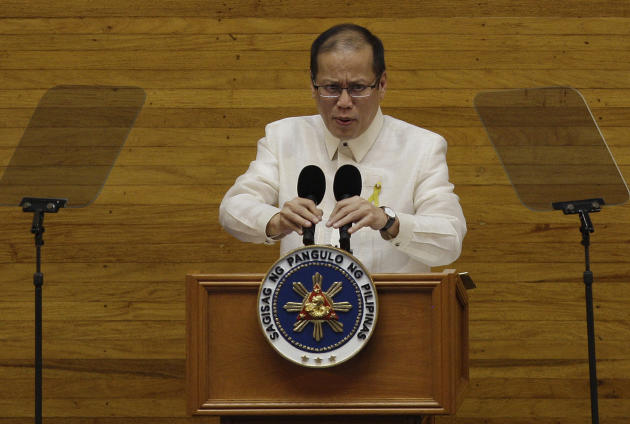 Philippine President Benigno Aquino III arranges the microphone before he delivers his State of the Nation Address during the 15th congress at the House of Representatives in suburban Quezon City, north of Manila, Philippines on Monday July 25, 2011. (AP Photo/Aaron Favila)