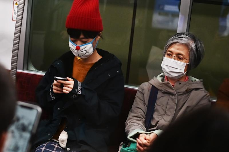 People wearing face masks travel on a train in Tokyo.