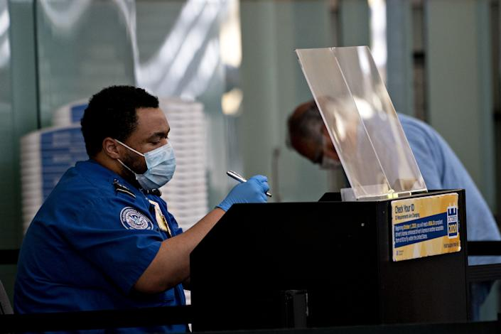 A Transportation Security Administration (TSA) agent wears a protective mask and sits behind a protective barrier while screening a traveler at Ronald Reagan National Airport (DCA) in Arlington, Virginia, U.S., on Tuesday, June 9, 2020. (Andrew Harrer/Bloomberg via Getty Images)