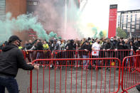 Fans move barriers outside the ground as they let off flares whilst protesting against the Glazer family, owners of Manchester United, before their Premier League match against Liverpool at Old Trafford, Manchester, England, Sunday, May 2, 2021. (Barrington Coombs/PA via AP)