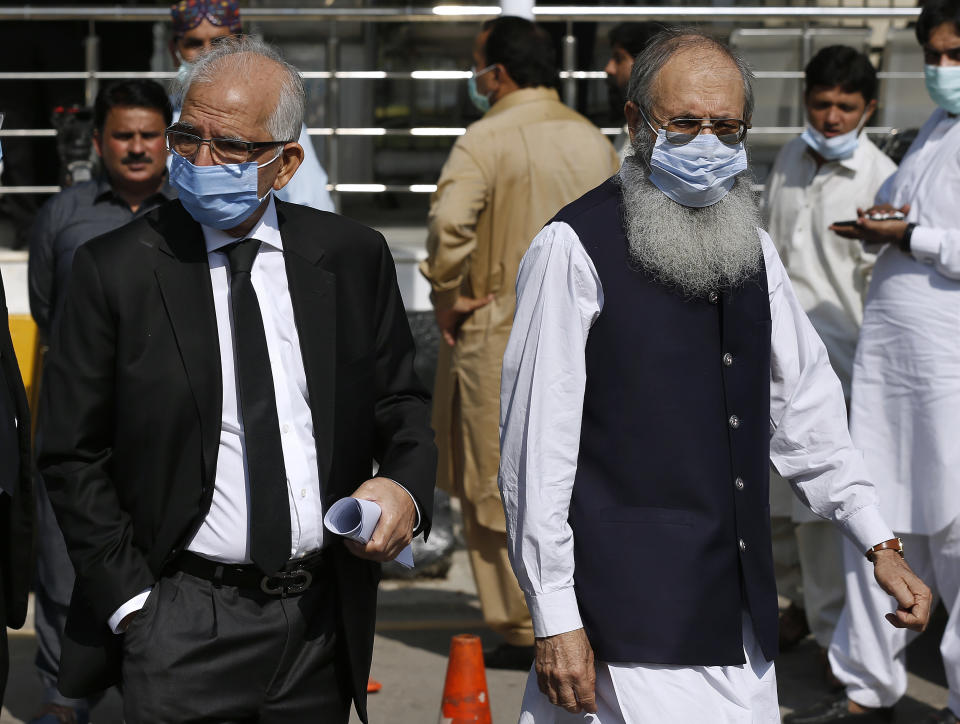 Ahmed Saeed Sheikh, right, father of a British-born militant Ahmed Omar Saeed Sheikh, leaves the Supreme Court with his lawyer Mahmood Ahmed Sheikh, left, after an appeal hearing in the Daniel Pearl case in Islamabad, Pakistan, Wednesday, Oct. 7, 2020. Ahmed Omar Saeed Sheikh, who has been on death row over the 2002 killing of U.S. journalist Daniel Pearl, will remain in jail for another three months under a government order, a prosecutor told the country's top court Wednesday, as it took up appeals of Pearl's family and government against acquittal of all accused of murder charges by another court. (AP Photo/Anjum Naveed)