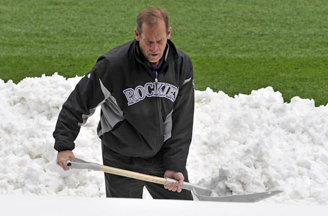 Colorado Rockies owner Dick Monfort shovels snow from the field before the start of a scheduled baseball double-header between the New York Mets and the Colorado Rockies on Tuesday, April 16, 2013, in Denver. (AP Photo/Jack Dempsey)