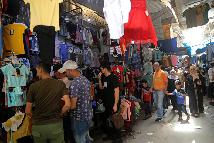Iraqis buy clothes in preparation for the Muslim holiday of Eid al-Fitr, which marks the end of the holy fasting month of Ramadan, at the Shorjah market in central Baghdad, Iraq, Tuesday, May 11, 2021. (AP Photo/Hadi Mizban)