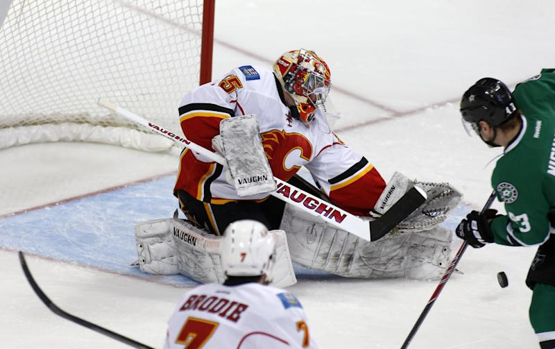 Calgary Flames goalie Joey MacDonald (35) makes a save against Dallas Stars right wing Valeri Nichushkin (43), of Russia, as Flames defenseman TJ Brodie (7) watches in the first period of an NHL hockey game on Friday, March 14, 2014, in Dallas. (AP Photo/Sharon Ellman)