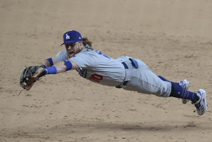 Dodgers third baseman Justin Turner dives, but can't corral a run-scoring double by Atlanta Braves shortstop Dansby Swanson.