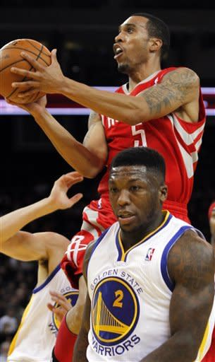 Houston Rockets' Courtney Lee (5) shoots over Golden State Warriors' Nate Robinson during the first half of an NBA basketball game, Sunday, Feb. 12, 2012, in Oakland, Calif. The Warriors won 106-97. (AP Photo/George Nikitin)