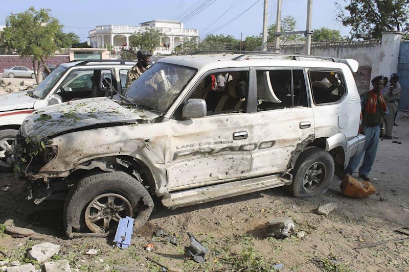 Somali soldiers walk near a destroyed car, after a two suicide bombers attacked a popular restaurant in Mogadishu, Somalia, Saturday Nov. 3, 2012. Three people, including two suicide bombers died in the attack. (AP Photo/Farah Abdi Warsameh)